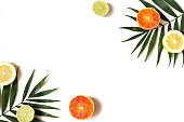 Exotic composition of fresh lemons, red oranges, lime fruit and lush green palm leaves isolated on white table background. Tropical summer vacation concept, flat lay, top view. Decorative frame.