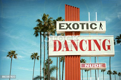 aged and worn exotic dancing sign with palm trees