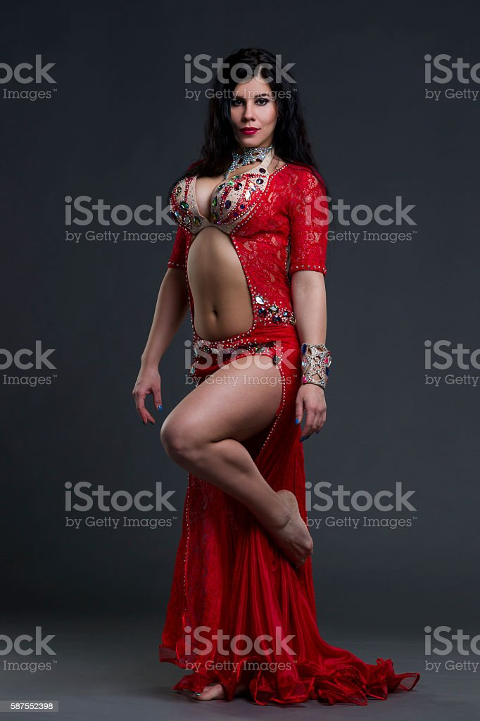 Exotic eastern women dance in red dress on gray background stock photo