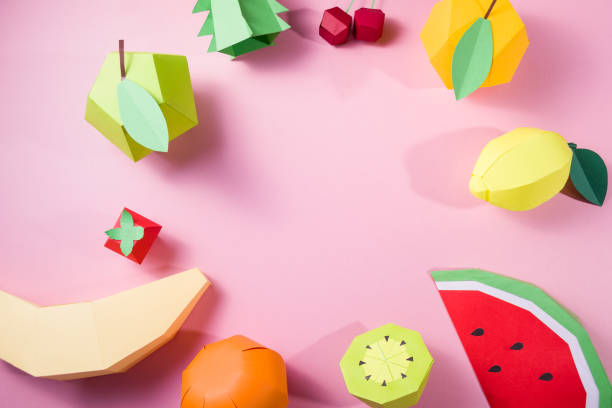 exotic fruits made of paper on pink background stock photo