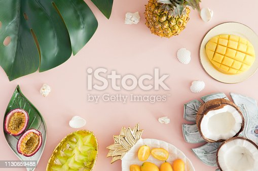 Exotic fruits on pastel pink background - pineapple, mango, coconut, carambola, passion fruit. Top view and flatlay