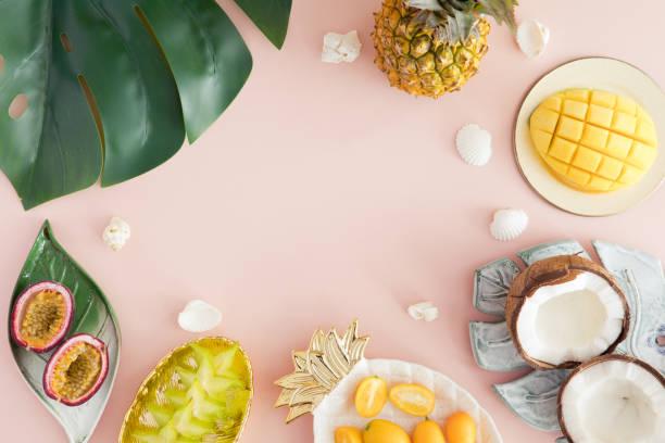 pastel pembe arka plan üzerinde egzotik meyveler-ananas, mango, hindistan cevizi, carambola, tutku meyve. üst görünüm ve flatlay - hindistan cevizi tropik meyve stok fotoğraflar ve resimler