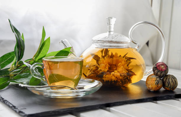 Exotic green tea with flowers in glass teapot stock photo