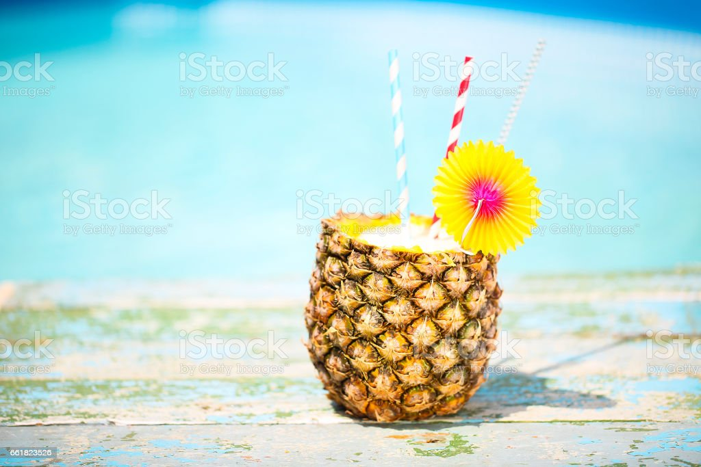 Exotic pineapple cocktail near pool. Pina colada stock photo