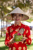 Exotic traditional Vietnamese girl while serving fresh coconut  fruit with flowers