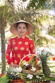 Exotic traditional Vietnamese girl with assorted tropical fruits basket