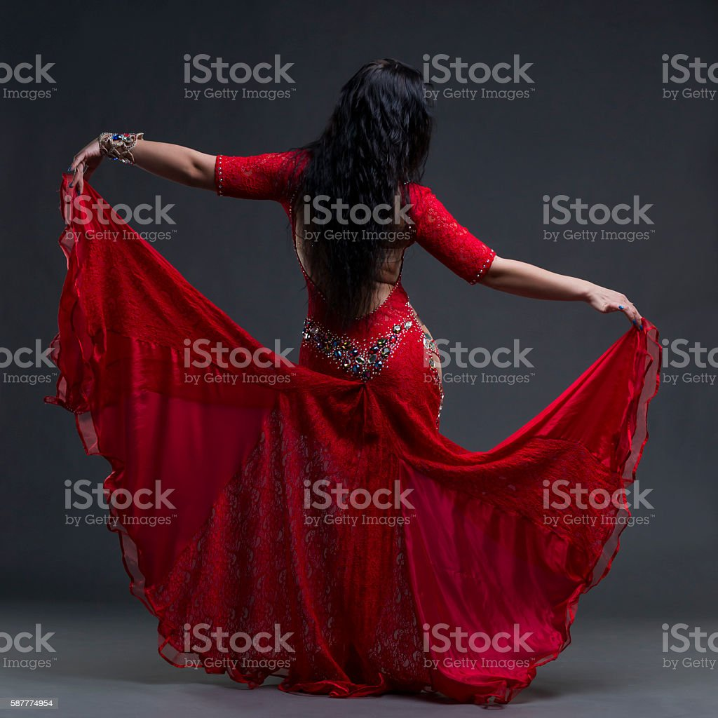 Exotic women dance in red dress with open back stock photo