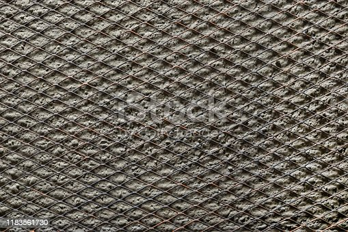 Full frame texture of expanded metal mesh on concrete wall background