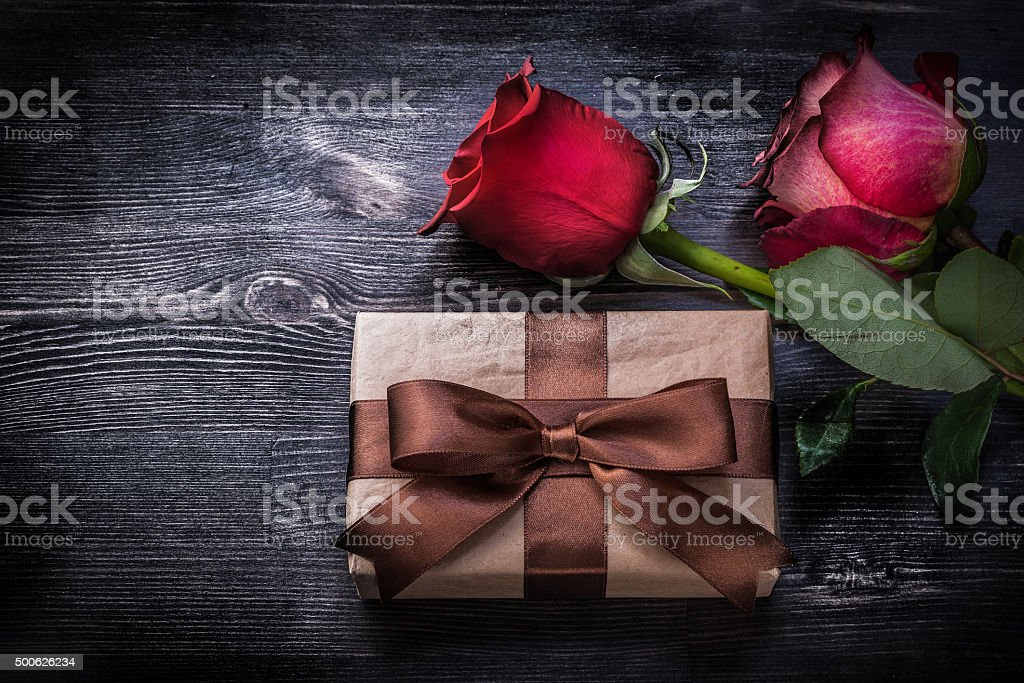 Expanded roses wrapped present box on wood board holidays concept.