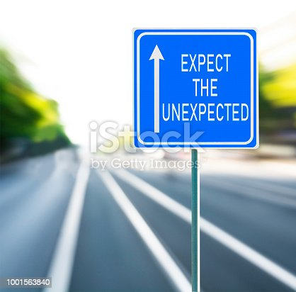 istock Expect the unexpected motivational phrase on blue road sign with arrow and blurred speedy background. Copy space. 1001563840