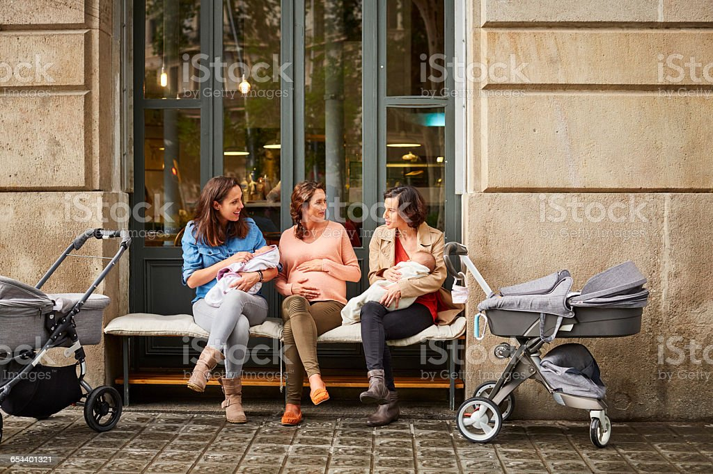 Expectant and friends with babies sitting on bench - foto de stock