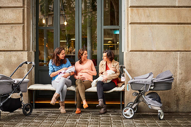 Expectant and friends with babies sitting on bench stock photo