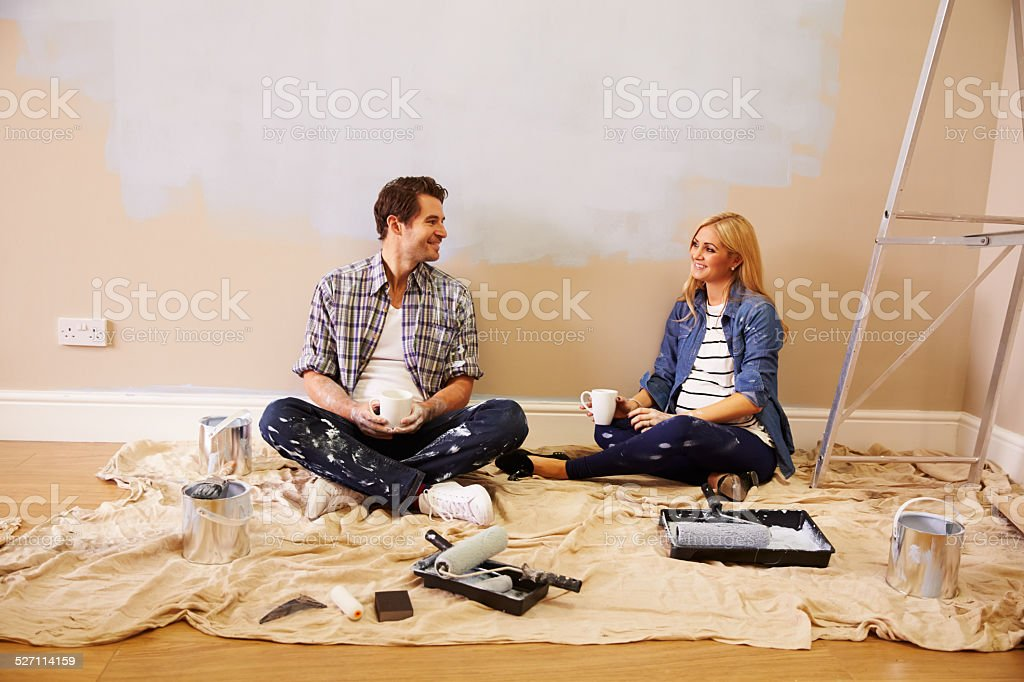 Expectant Couple Taking A Break Whilst Decorating Nursery royalty-free stock photo