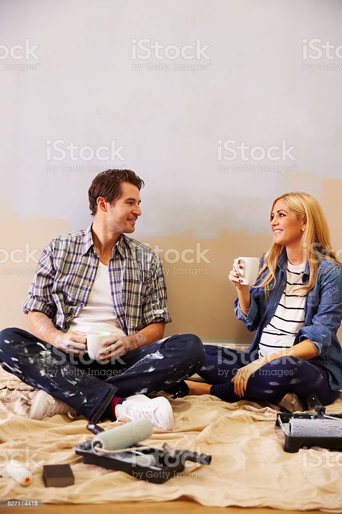 Expectant Couple Taking A Break Whilst Decorating Nursery stock photo