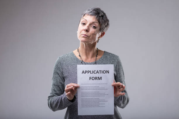 Expectant woman holding up an application form stock photo