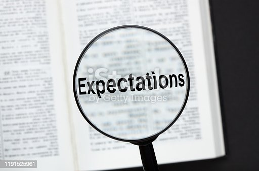 The word Expectations with magnifying glass over a opened book on black background