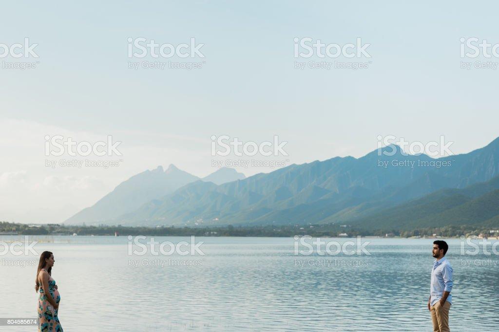 Expecting couple standing apart next to lake stock photo
