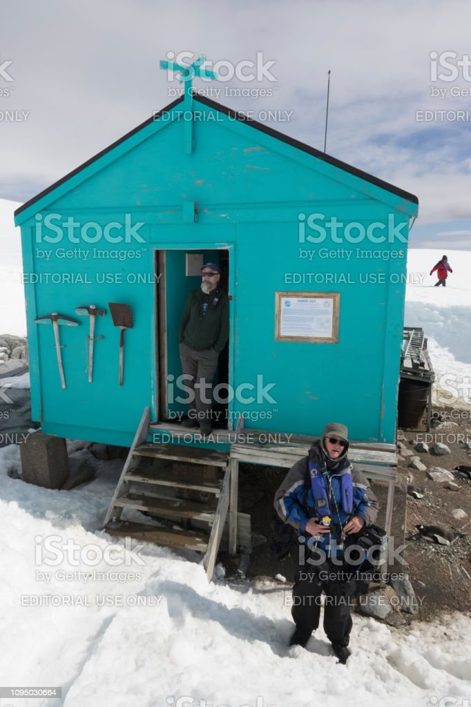Expedition guides Damoy Hut nesting gentoo penguins Wiencke Island Antarctic Peninsula Antarctica stock photo