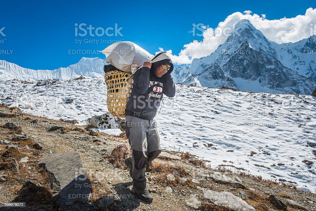 Expedition porter carrying traditional Sherpa wicker basket Himalaya mountains Nepal stock photo