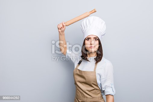 Expel penalty humorous joke bad concept. Portrait of pretty sad upset laughable annoyed irritated chef with raised wooden pin in hand wants to beat you unskilled assistant isolated on gray background