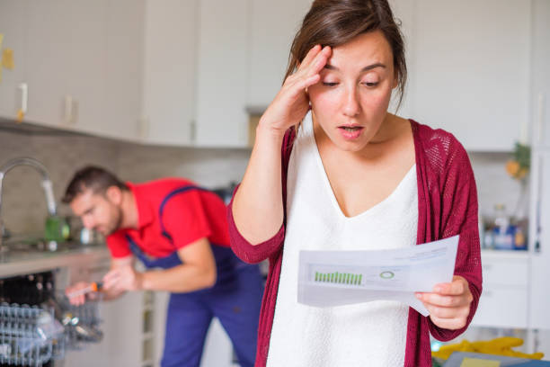 Expensive appliance repair costs and sad woman Housewife shocked after reading repair cost estimate of domestic appliance expense stock pictures, royalty-free photos & images