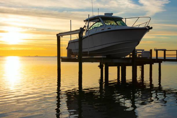 Expensive fishing boat on motorized electric dock vessel lift at sunrise stock photo