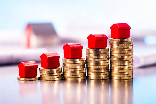 Expensive real estate Small red houses standing on stacks of coins with blueprints and architectural model in the background. expense stock pictures, royalty-free photos & images