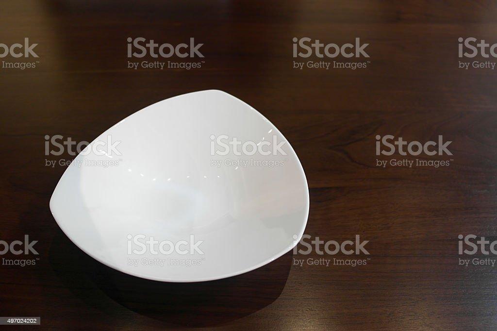 Expensive triangular shaped luxury porcelain plate on oak table setting stock photo