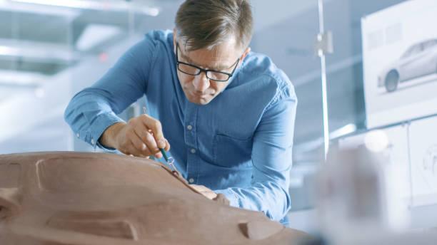 erfahrung-automobil-designer mit einer harke formt prototyp auto-modell aus plastilin ton. er arbeitet in einem modernen studio in einem großen automobilunternehmen hauptquartier. - skulpturprojekte stock-fotos und bilder