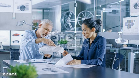 istock Experienced Automotive Designer and Female Engineer Works with a Concept Car Prototype Model, Perfecting it and Making Design Corrections. They Work in a Stylish, Bright, Modern Office. 921019832