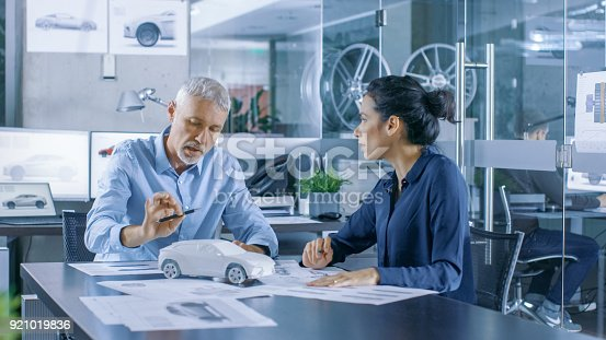 istock Experienced Automotive Designer and Female Engineer Works with a Concept Car Prototype Model, Perfecting it and Making Design Corrections. They Work in a Stylish, Bright, Modern Office. 921019836