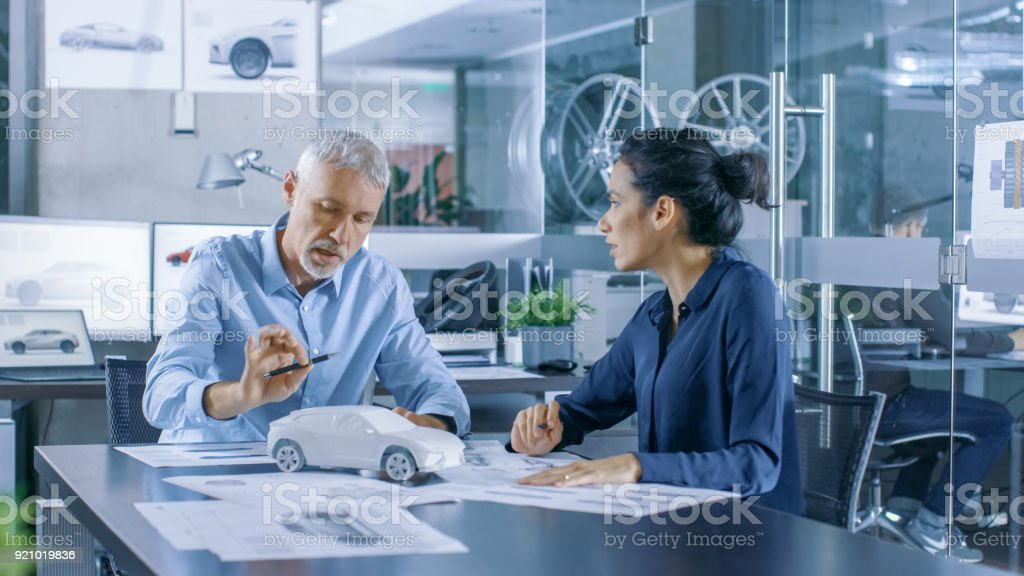 Experienced Automotive Designer and Female Engineer Works with a Concept Car Prototype Model, Perfecting it and Making Design Corrections. They Work in a Stylish, Bright, Modern Office. stock photo