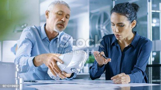 istock Experienced Automotive Designer and Female Engineer Works with a Concept Car Prototype Model, Perfecting it and Making Design Corrections. They Work in a Stylish, Bright, Modern Office. 921019902