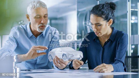 istock Experienced Automotive Designer and Female Engineer Works with a Concept Car Prototype Model, Perfecting it and Making Design Corrections. They Work in a Stylish, Bright, Modern Office. 921019930