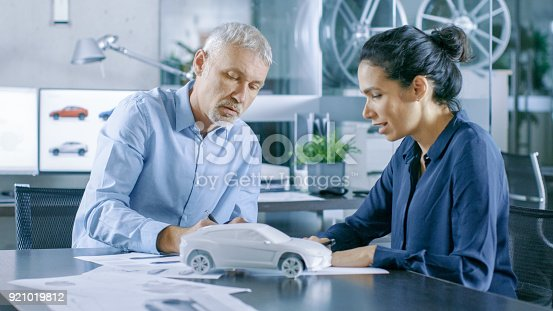 istock Experienced Automotive Designer and Female Engineer Works with Blueprints and Sketches of a New Car Prototype Model. 921019812