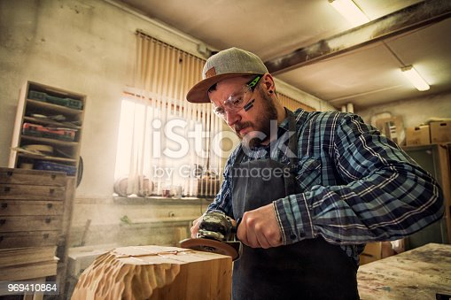 Experienced carpenter in work clothes and small buiness owner working in woodwork workshop, processes the board with an angle grinder, on the table is a hammer and many tools