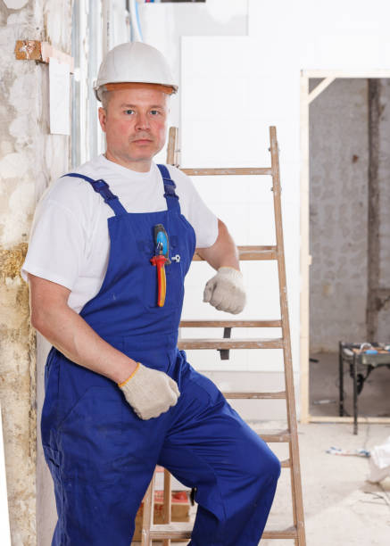 Experienced construction worker Portrait of experienced construction worker standing at indoors building site approbation stock pictures, royalty-free photos & images