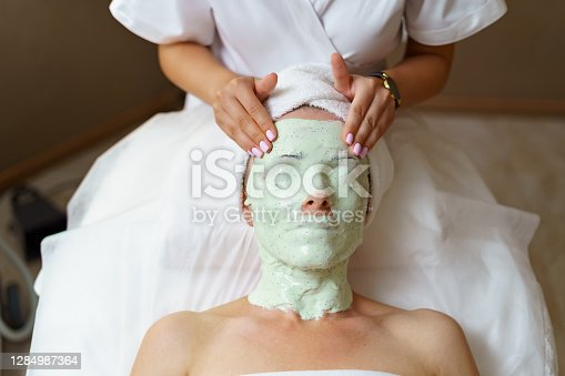 istock Experienced cosmetician removing alginate mask from a face of a caucasian woman. 1284987364
