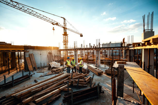 Experienced engineer explaining the problems in construction works - development after recession Construction industry concept - architects and engineers discussing work progress between concrete walls, scaffolds and cranes. construction industry stock pictures, royalty-free photos & images