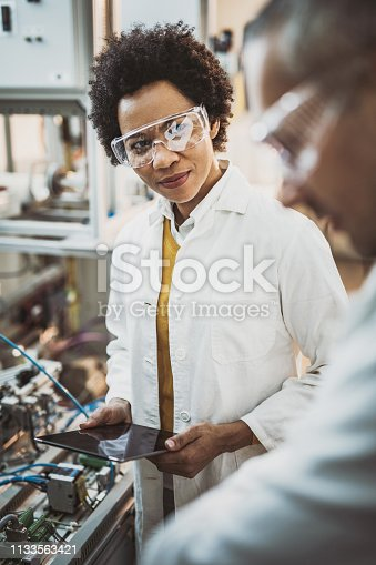Two mid adult lab workers working together on test machine in laboratory. Focus is on women.