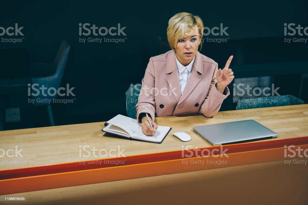 Experienced female coach writing down notes in notepad while...
