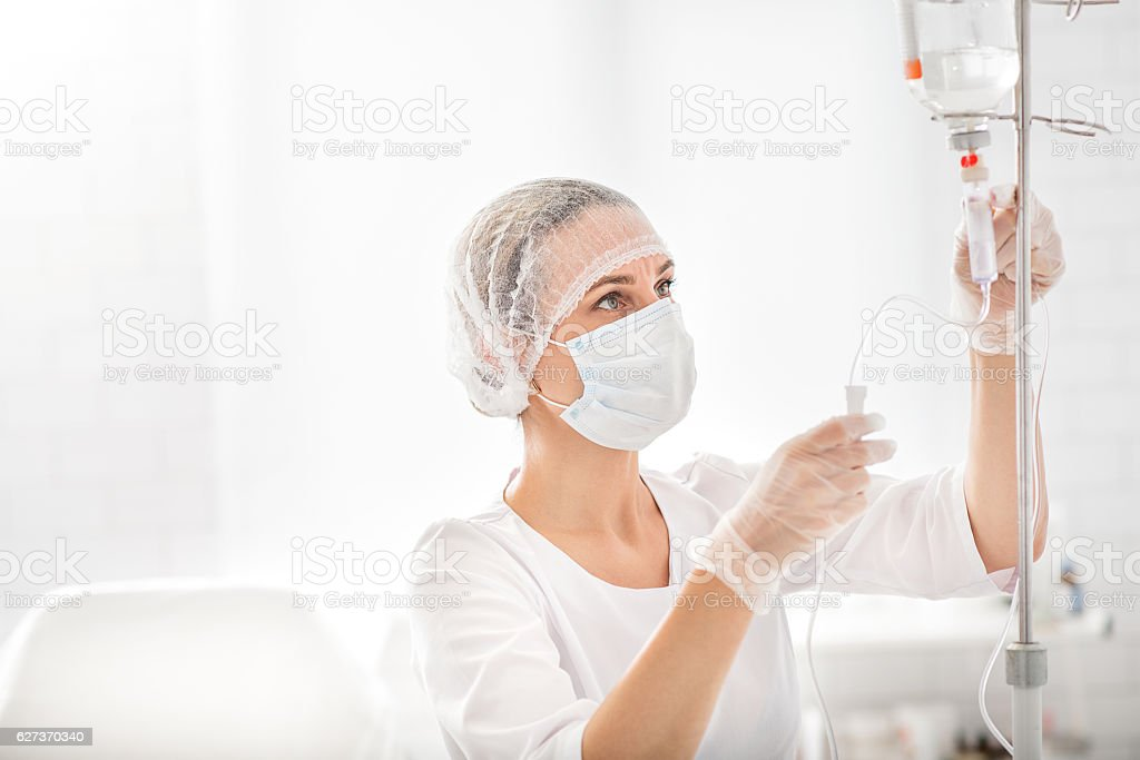 Experienced female doctor putting drip stock photo