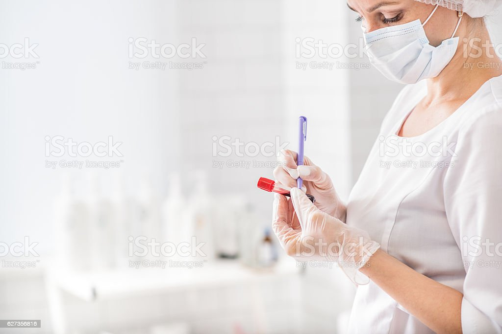 Experienced general practitioner writing on blood flask stock photo