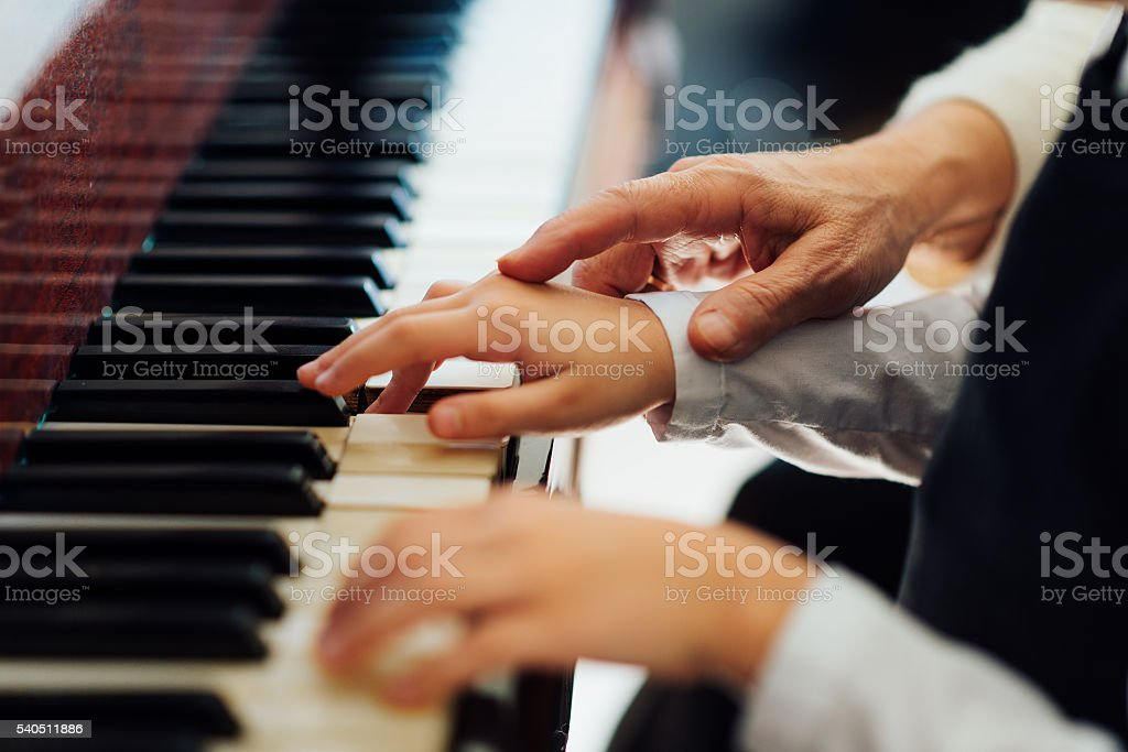 experienced hand of  old music teacher helps  child  pupil stock photo