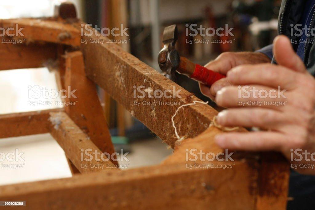 ervaren handen van een Australische Man herstellen en terugzetten van een houten stoel, voorbereiden om te worden bekleed in hun lokale winkel - Royalty-free Alleen mannen Stockfoto