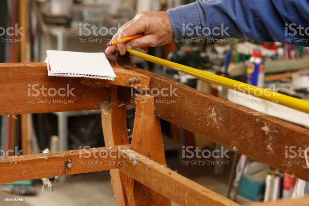 experienced hands of an Australian Man repairing and restoring a wooden chair, preparing it to be upholstered in their local store - Royalty-free Adult Stock Photo
