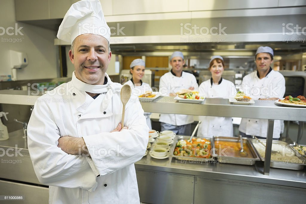 Experienced head chef posing proudly in a modern kitchen stock photo