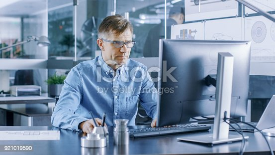 istock Experienced Industrial Engineer Working on Personal Computer in the Stylish, Modern, Glass Office. 921019590