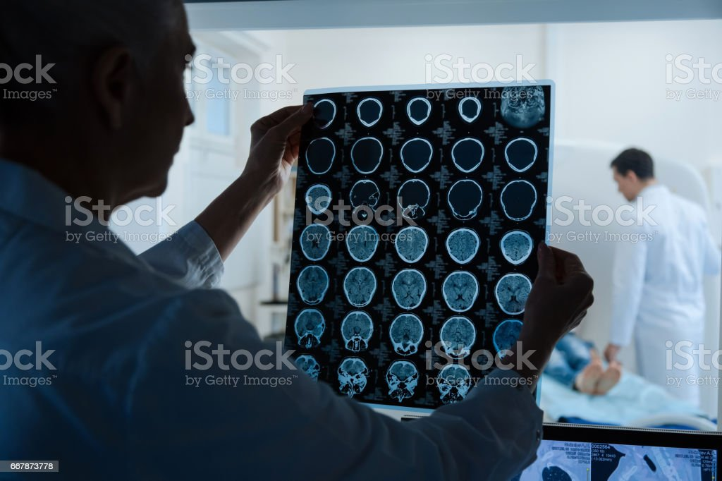 Experienced intelligent oncologist looking at the MRI scan results stock photo