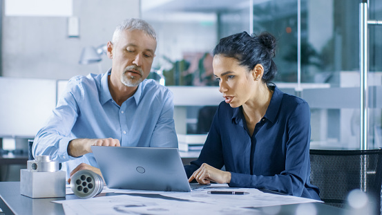 istock Experienced Male and Female Industrial Engineers Discuss ongoing Project while Working on a Laptop. They Design Machinery Component. 921020080